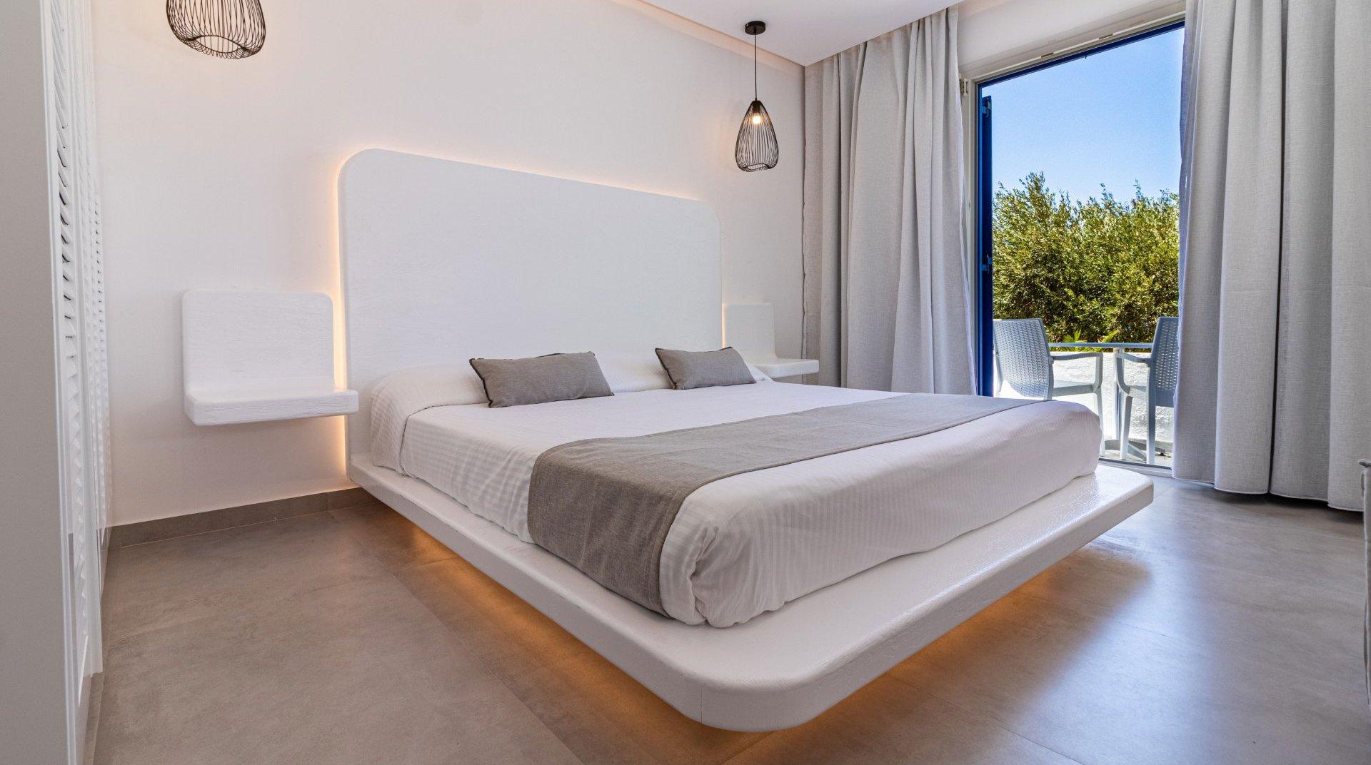 Το εσωτερικό του δωματίου με το κρεβάτι και τα φώτα από γύρω, τα μοντέρνα κομοδίνα και μια ματιά από το μπαλκόνι με τις καρέκλες και τον ουρανό