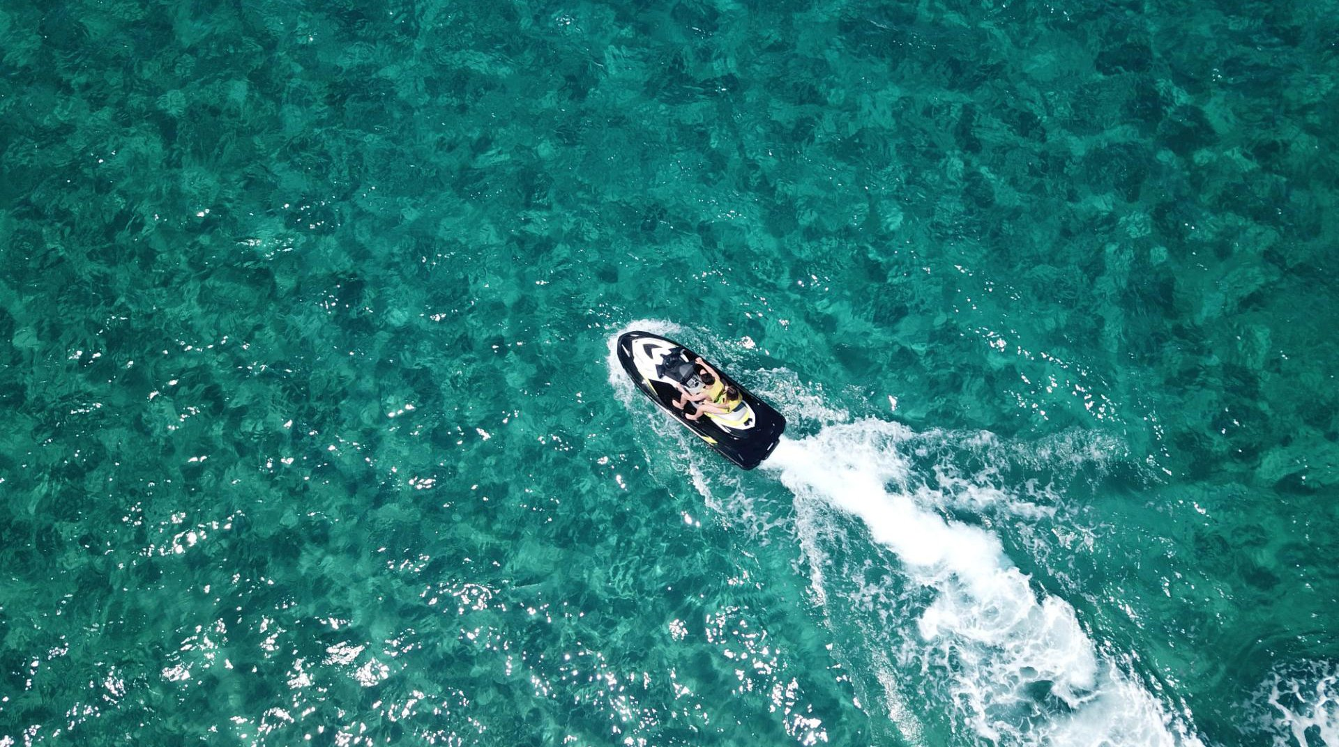 Two persons jet skiing in the sea of Mykonos