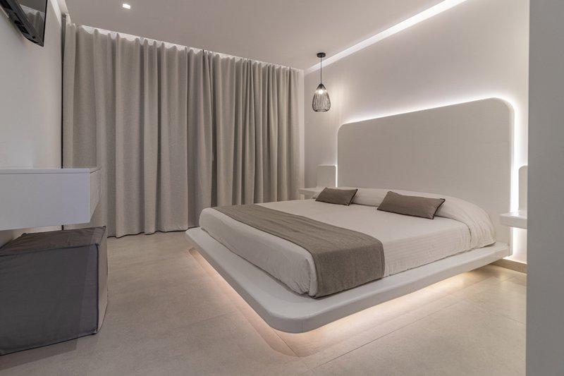 Το εσωτερικό του δωματίου με το κρεβάτι και τα φώτα από γύρω, τα μοντέρνα κομοδίνα, το γραφείο και τις κλειστές κουρτίνες