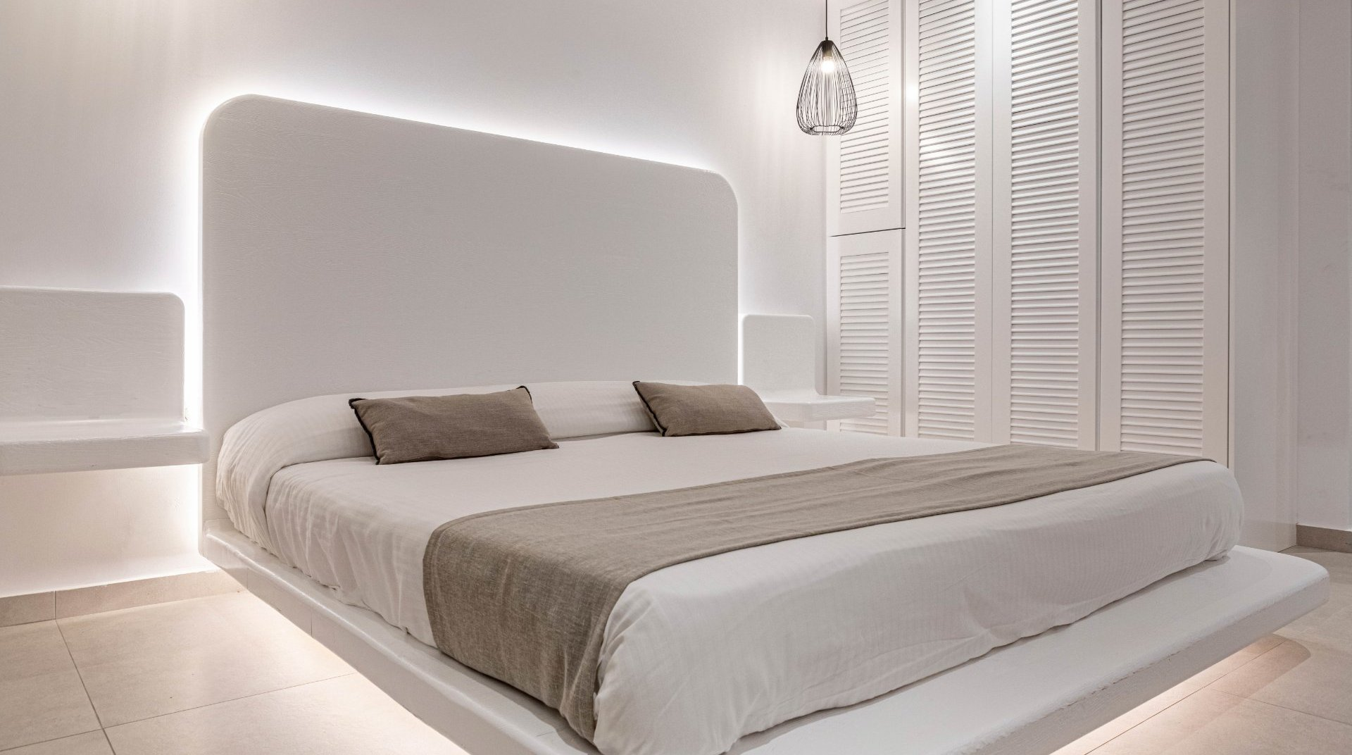 The interior of the Daylight Wing room with the bed and the underlights, the modern bedside tables and the closet
