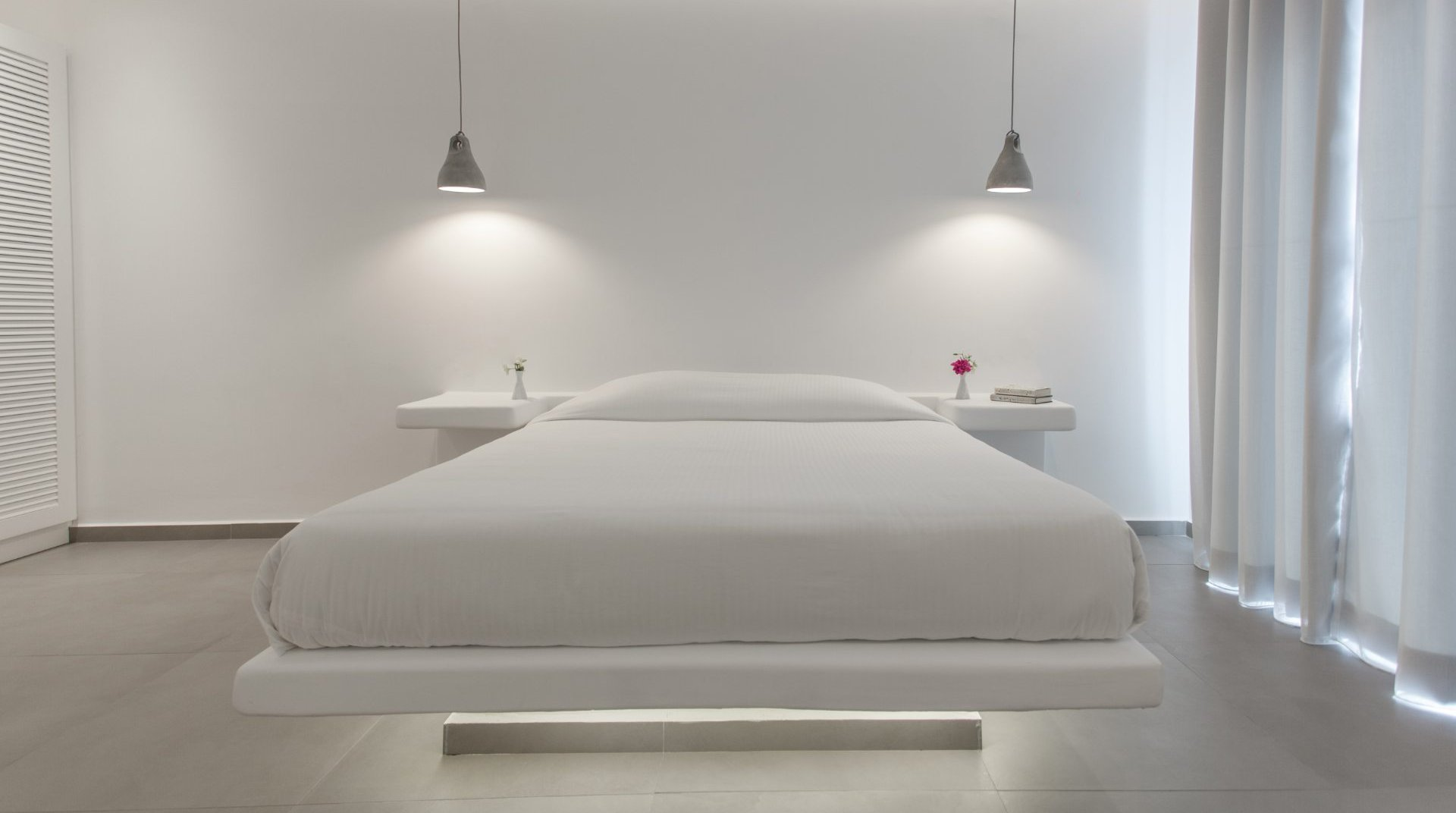 The interior of the suite with the bed, the modern bedside tables and the closet