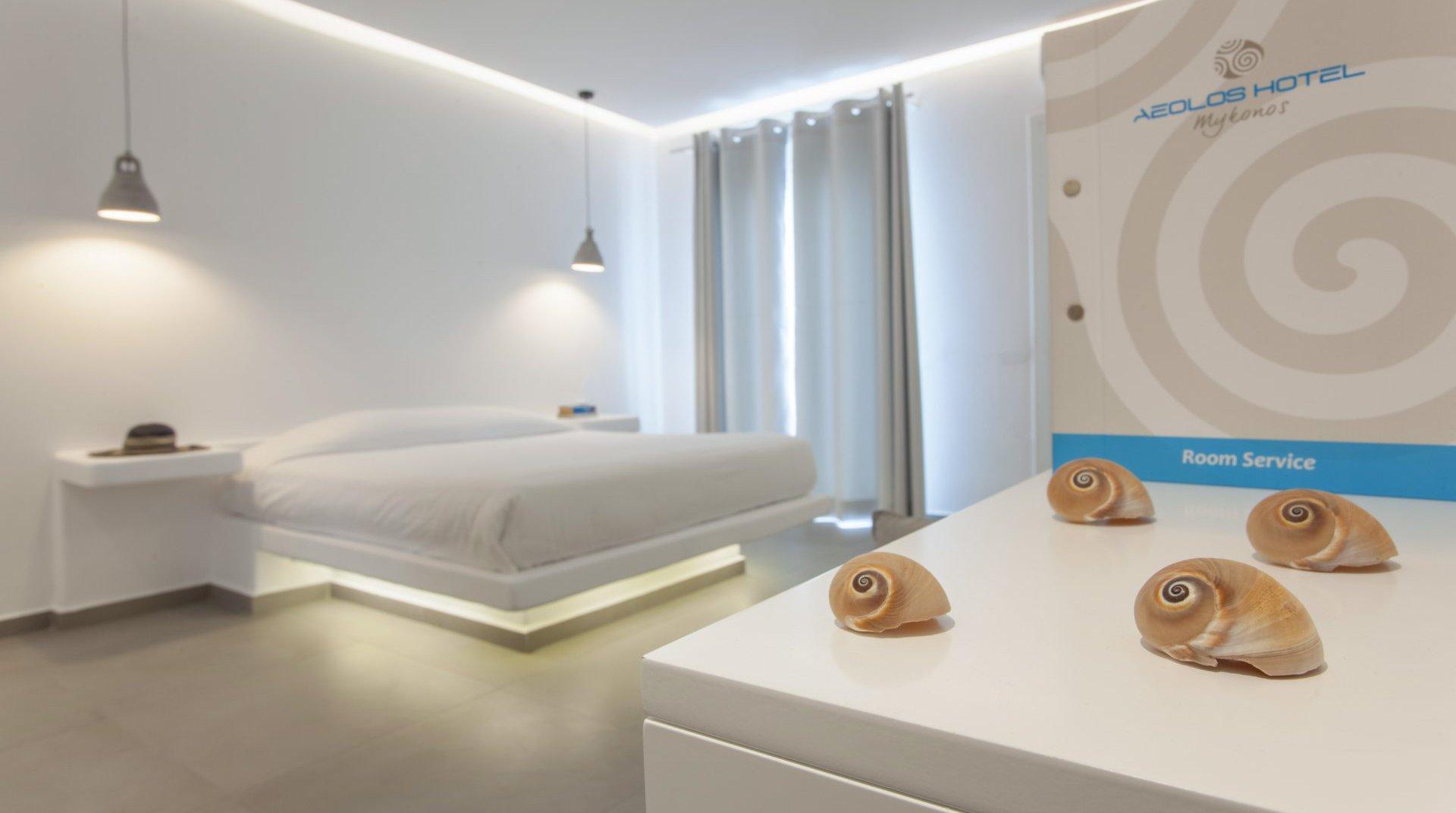 Το εσωτερικό του δωματίου με τον κατάλογο του Room Service, και από πίσω το κρεβάτι με τα φώτα από κάτω και τα φωτιστικά στο ταβάνι.