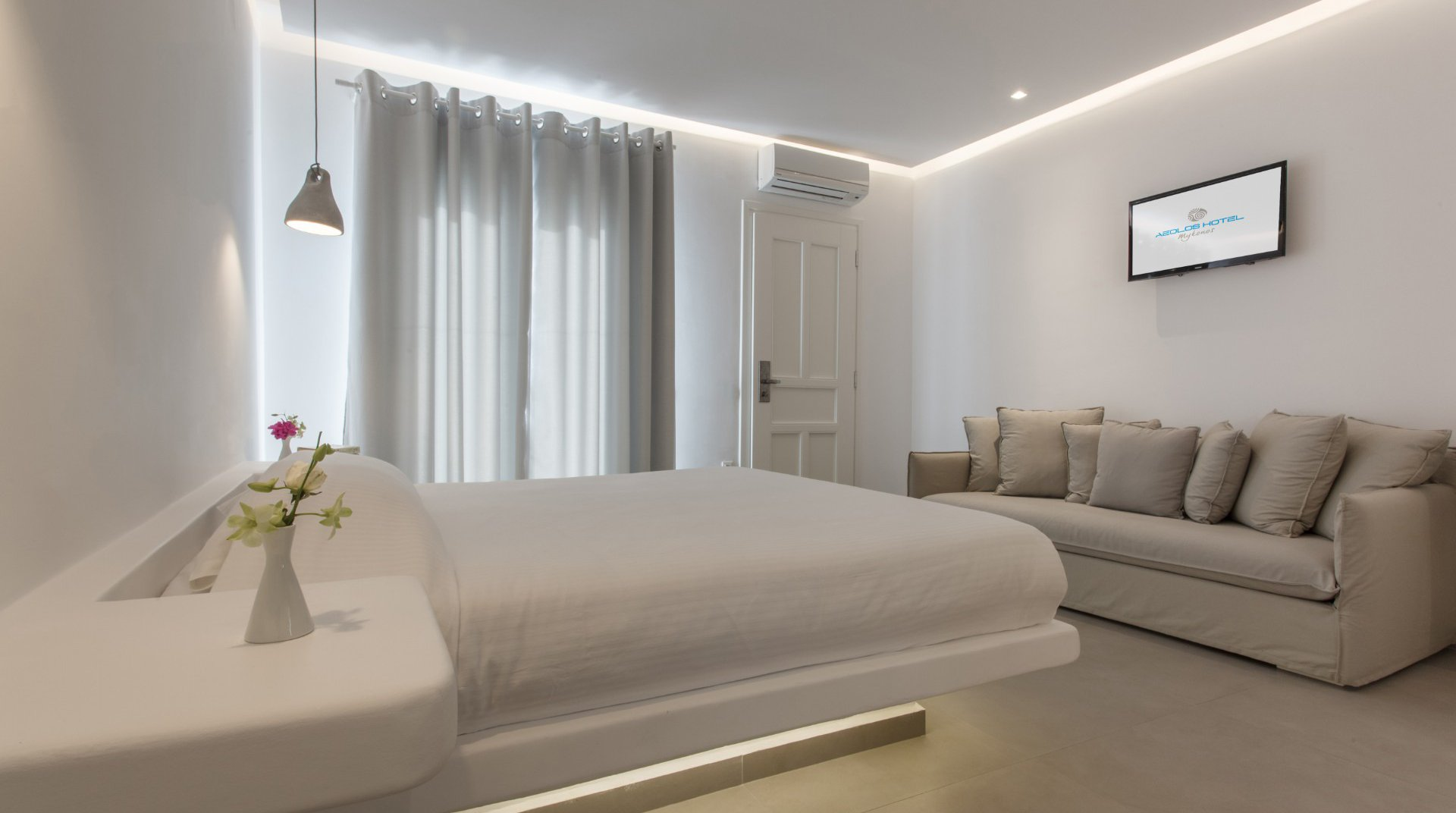 The interior of the suite with the bed,, the modern bedside tables, the sofa, the TV