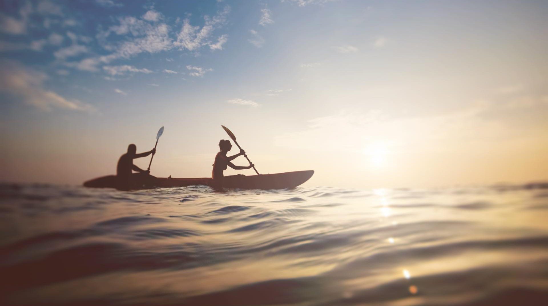 A man and a woman kayaking on the seas of Mykonos