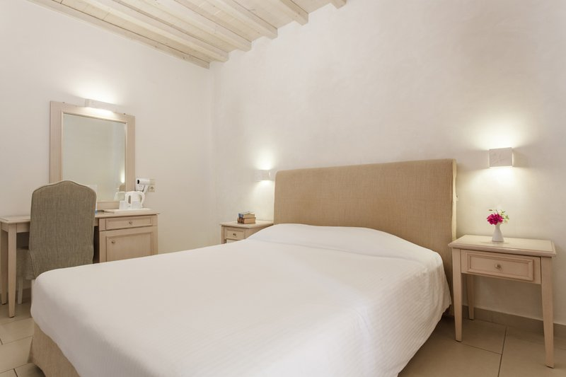 The interior of the room with the double bed, the bedside tables, the desk, the chair and the mirror
