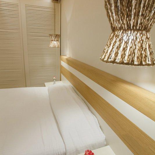 Το εσωτερικό του δωματίου από τον αέρα με το κρεβάτι, το φωτιστικό και την ντουλάπα