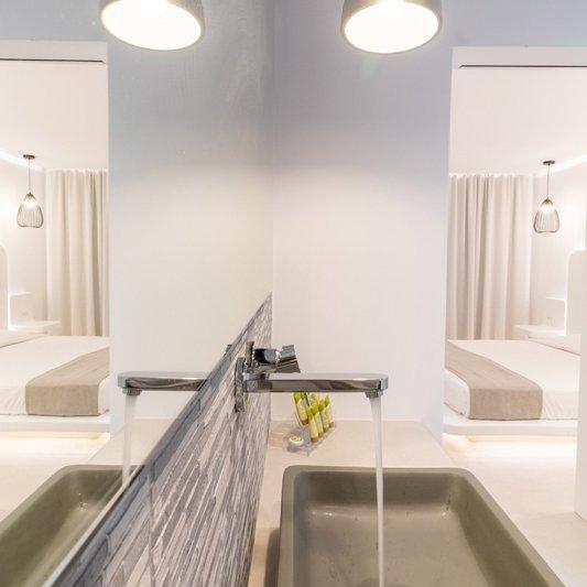 Το λουτρό του δωματίου με τον νεροχύτη, τα φώτα, τον καθρέπτη, και τον ευρύχωρο πάγκο