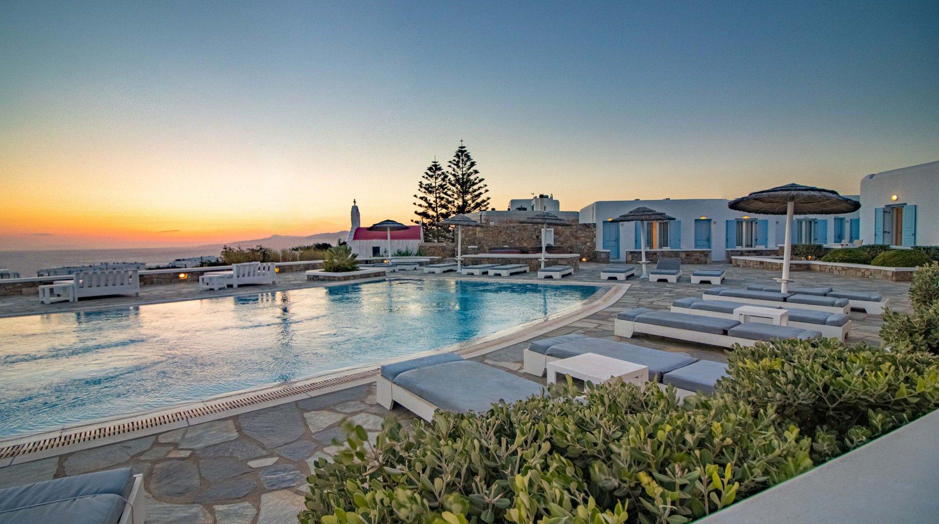 Το Sunset Wing το ηλιοβασίλεμα με την πισίνα, τις ξαπλώστρες, τα εξωτερικά κρεβάτια και την πρασινάδα