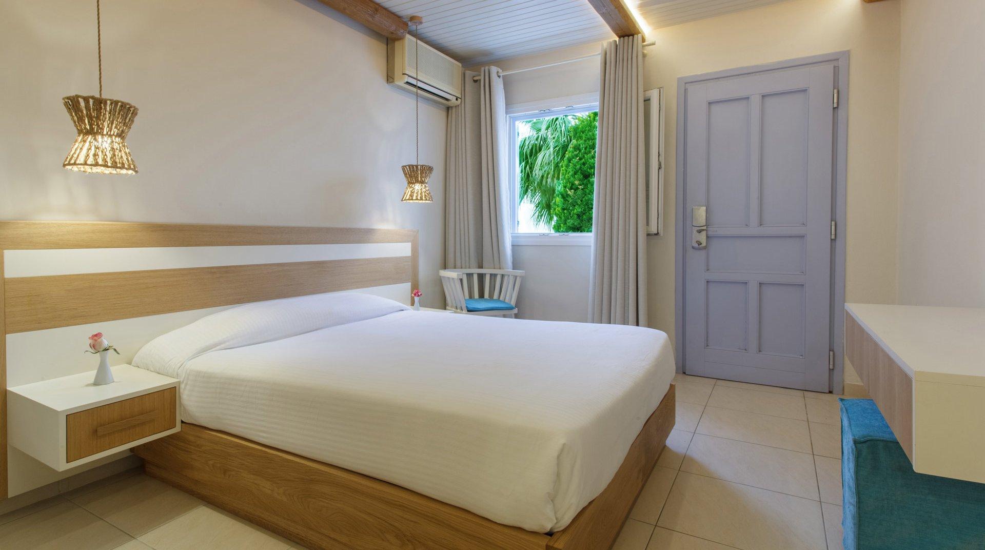 Το εσωτερικό του δωματίου με το κρεβάτι, την καρέκλα και το γραφείο