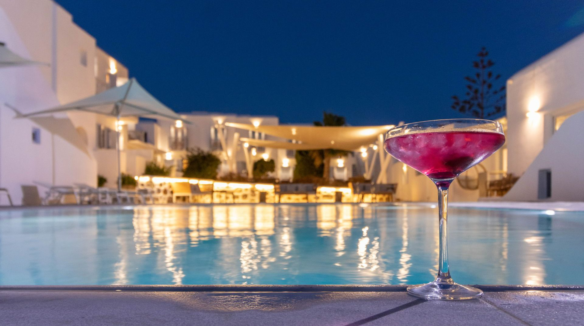 The pool of the Main Section during night time with a cocktail and the restaurant in the background