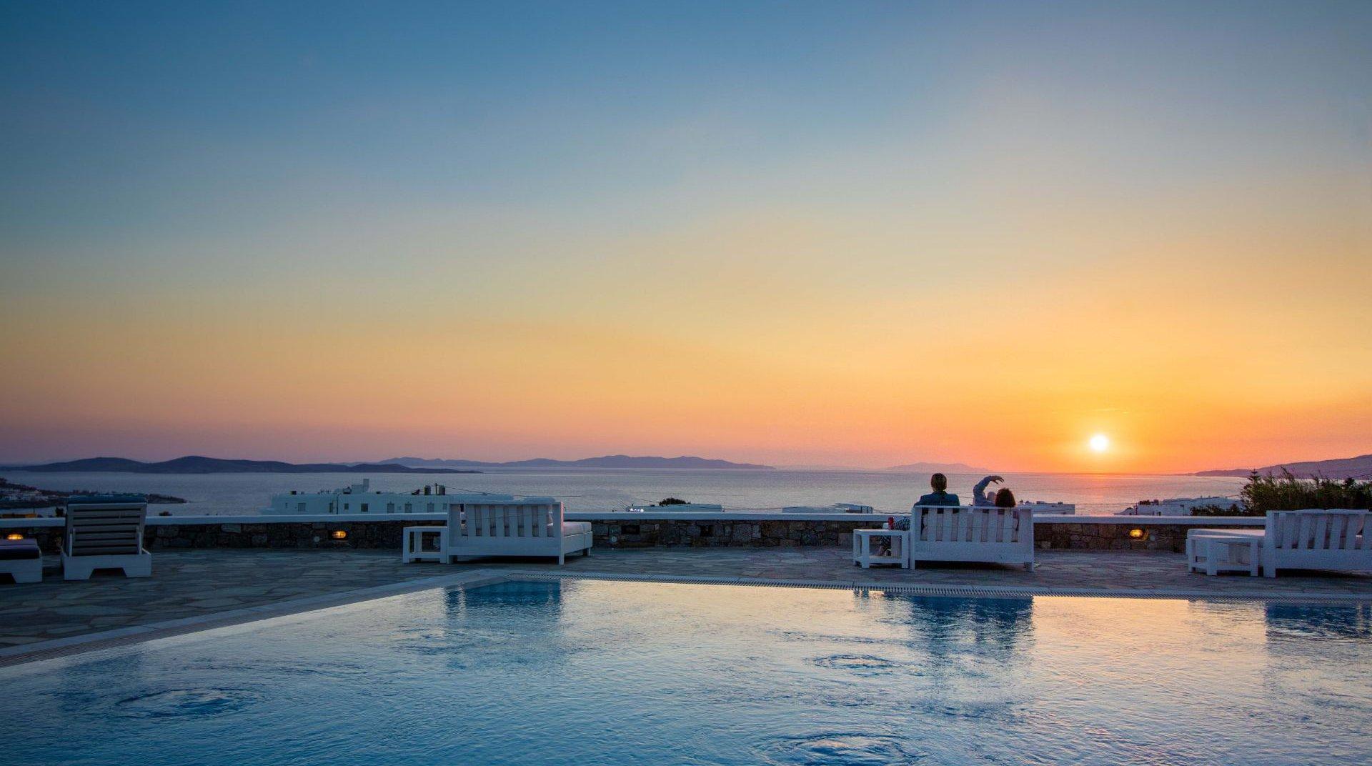 Το Sunset Wing με τα εξωτερικά κρεβάτια, την πισίνα και ένα ζευγάρι να απολαμβάνει το ηλιοβασίλεμα