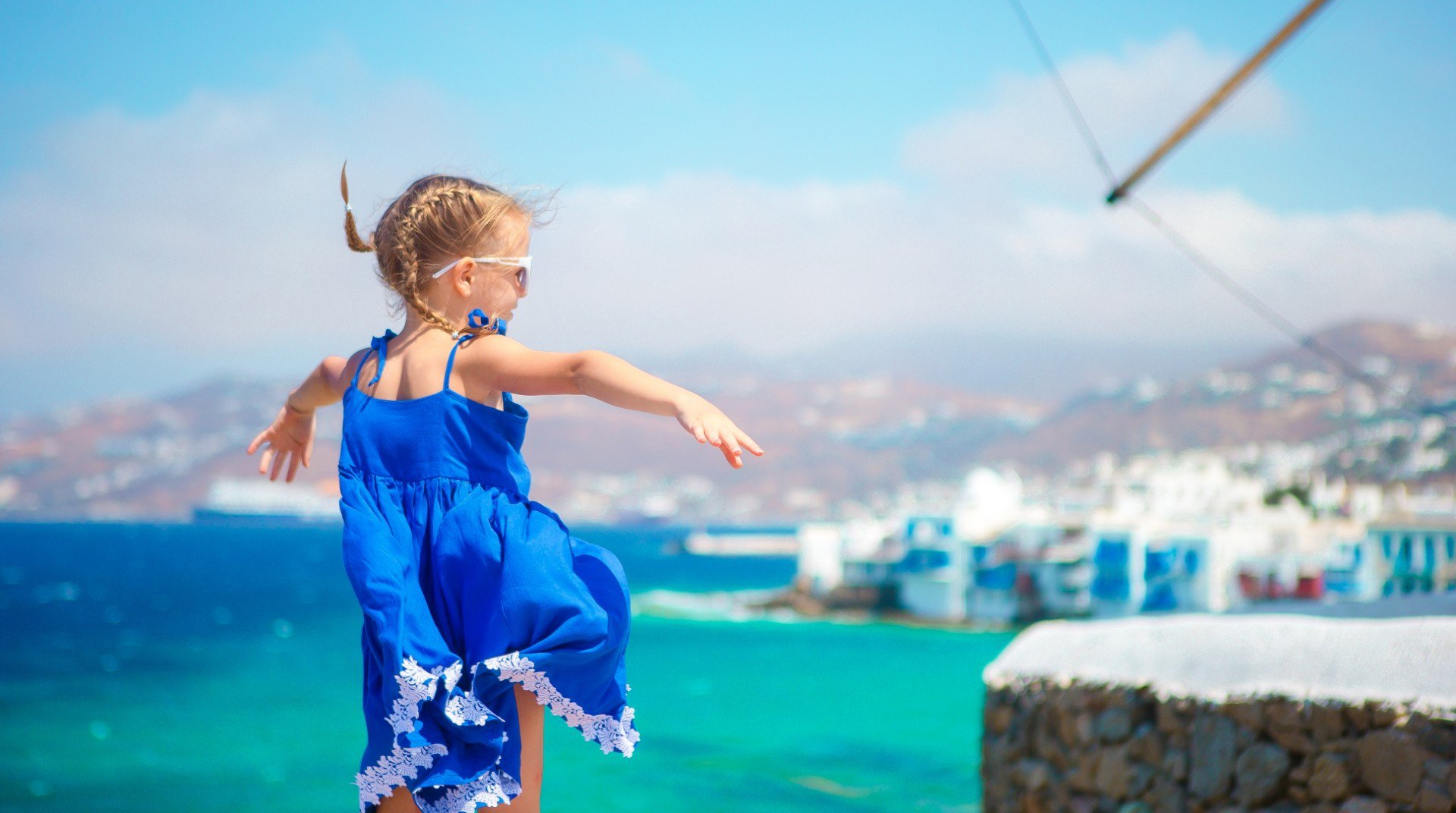 A child playing with the view of Chora in the background