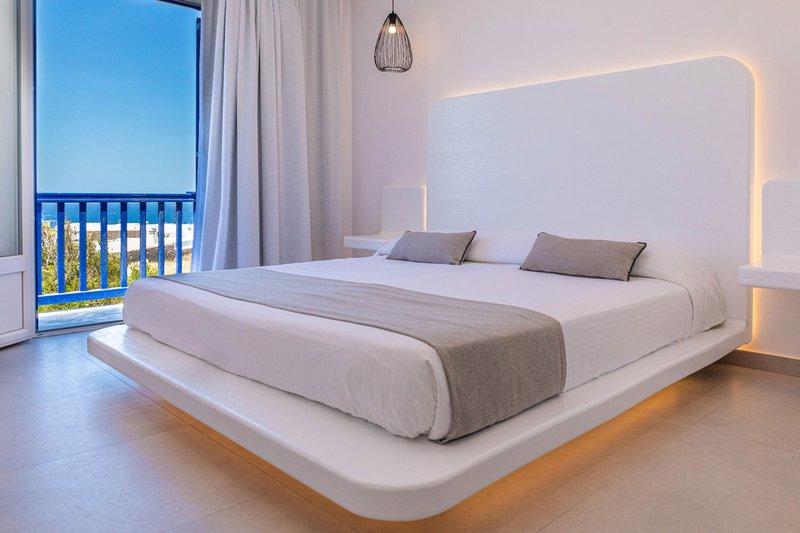 Το εσωτερικό του δωματίου με το κρεβάτι και τα φώτα από γύρω, τα μοντέρνα κομοδίνα και μια ματιά από μια ματιά από την υπέροχη θέα στην θάλασσα και τον γαλανό ουρανό
