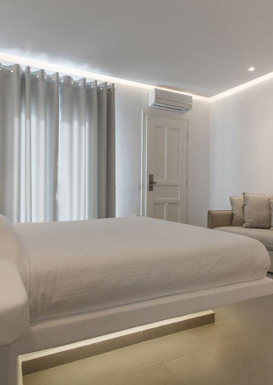 Το εσωτερικό της σουίτας του Sunset Wing με το κρεβάτι, τον καναπέ, την τηλεόραση, τον καθρέπτη και το τραπεζάκι
