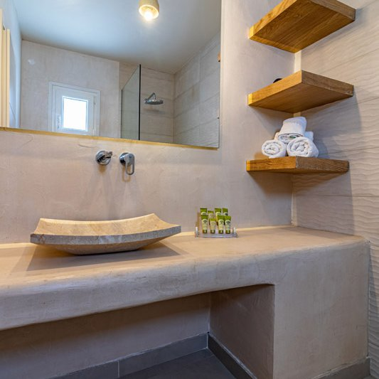 The luxurious bathroom with the washbasin, the towels and the mirror