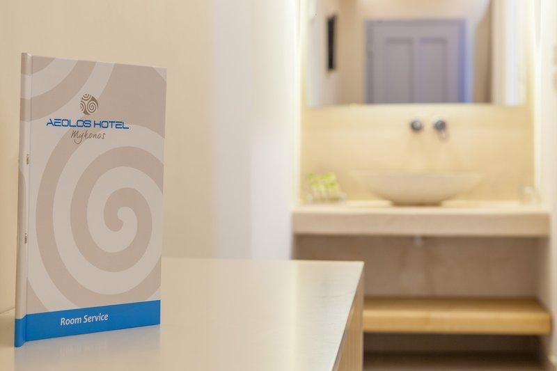 Το εσωτερικό του δωματίου με τον κατάλογο του Room Service, και τον νιπτήρα με τον καθρέπτη