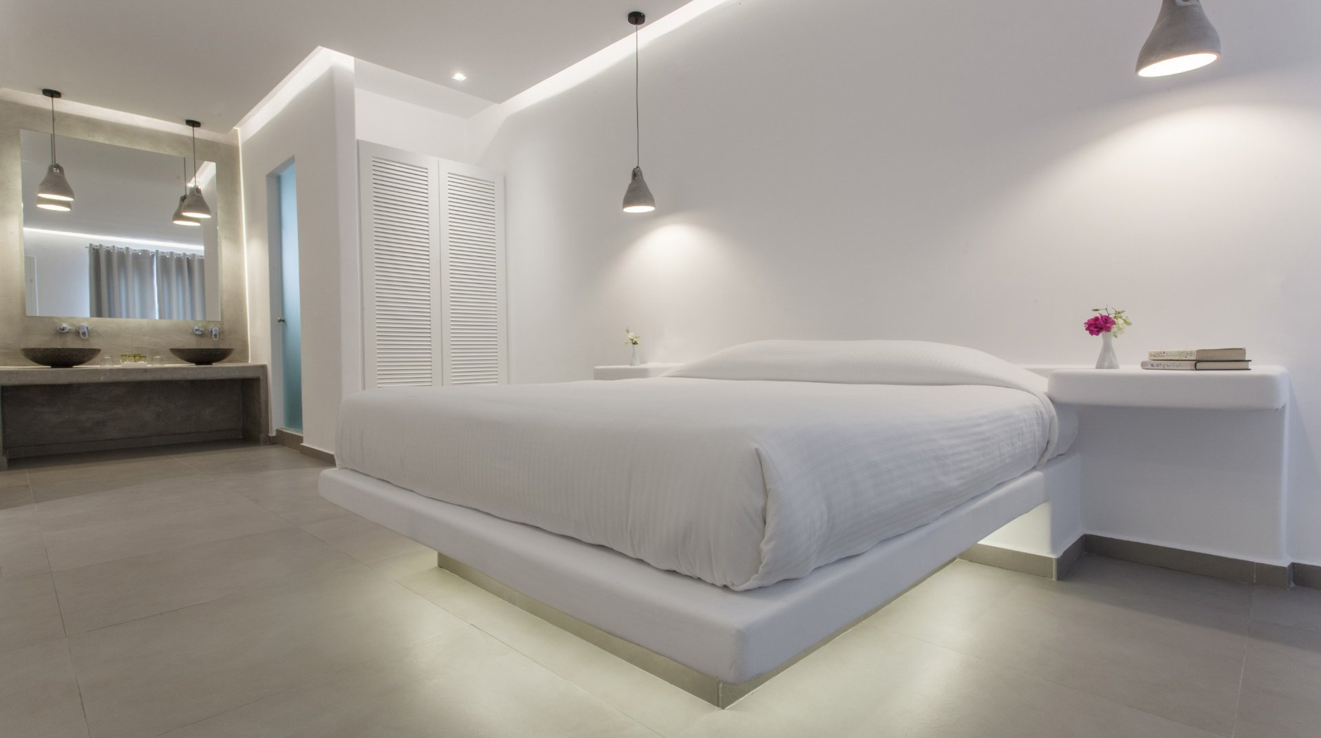 The interior of the suite with the bed, the closet, and in the background the spacious counter with the modern sinks and the huge mirror