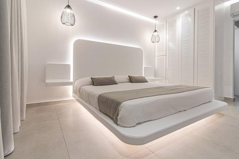 Το εσωτερικό του δωματίου με το κρεβάτι και τα φώτα από γύρω, τα μοντέρνα κομοδίνα και την ντουλάπα