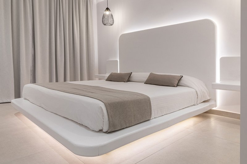 Το εσωτερικό του δωματίου με το κρεβάτι και τα φώτα από γύρω, τα μοντέρνα κομοδίνα και τις κουρτίνες στην μπαλκονόπορτα