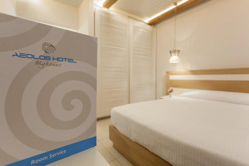 Το εσωτερικό του δωματίου με τον κατάλογο του Room Service, το κρεβάτι και την ντουλάπα