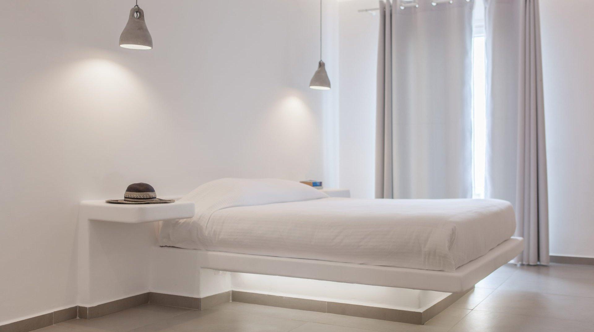 Το εσωτερικό του δωματίου με το κρεβάτι, τα φωτιστικά, τα κομοδίνα και τις κουρτίνες στην μπαλκονόπορτα