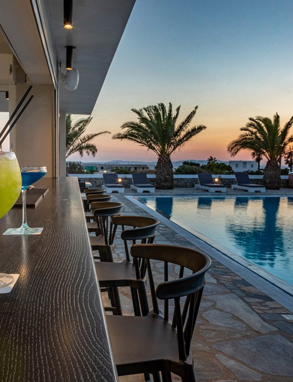 The pool bar of the Daylight Wing during the sunset with the cocktails, the pool, and the sunbeds with the palm trees