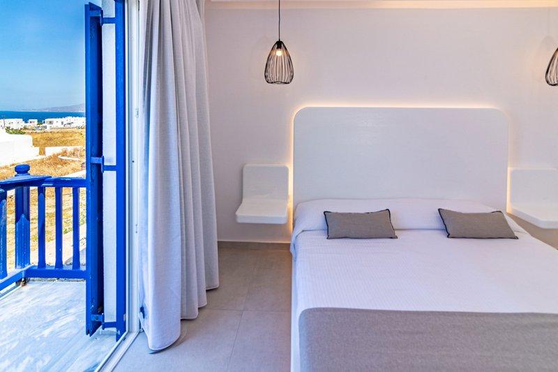 Το εσωτερικό του δωματίου από την μία πλευρά, με το κρεβάτι, το κομοδίνο και μια ματιά της υπέροχης θέας στην θάλασσα από το μπαλκόνι