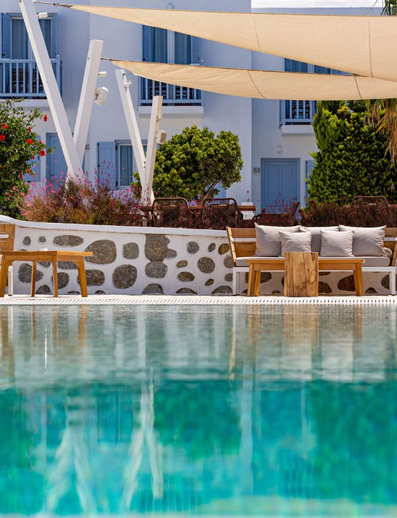 The pool of the Main Section with the outdoor sofas and the plants around the restaurant