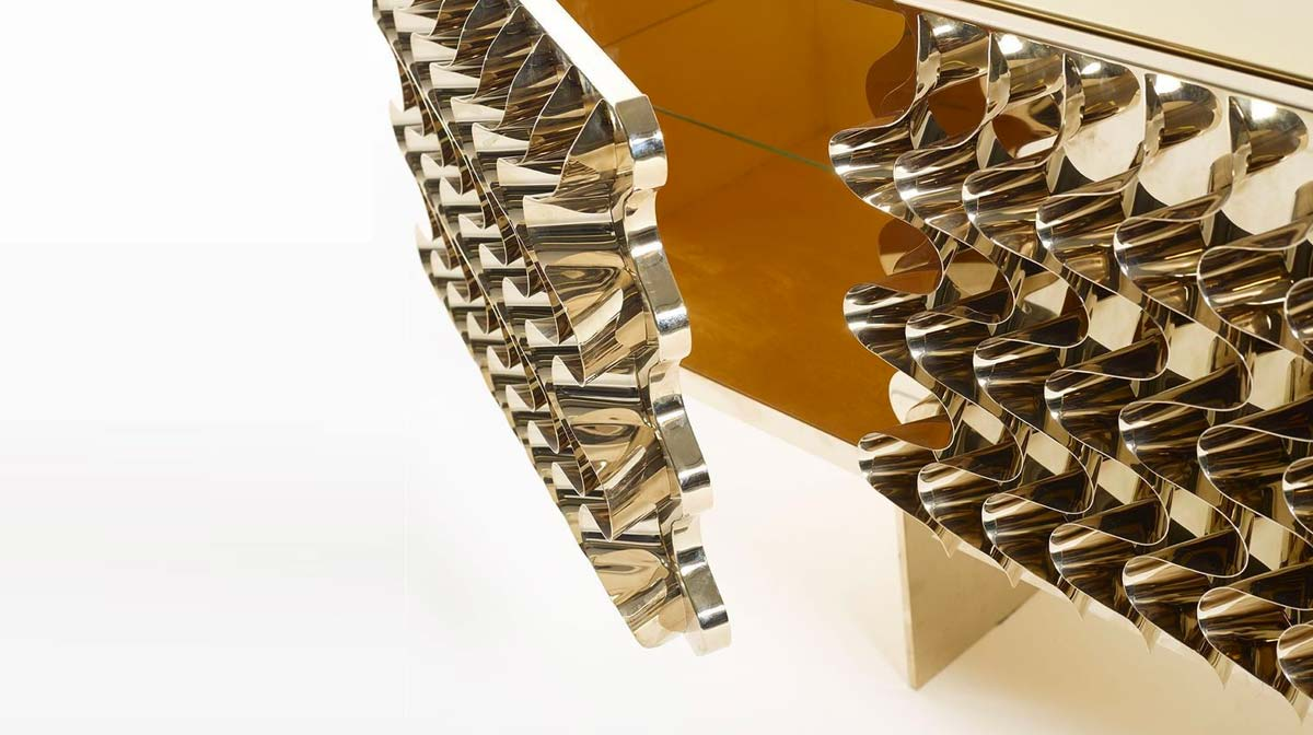 By Maurizio Galante & Tal Lancman for Opinion Ciatti, Waves is a shimmering console, embellished with sculptural wave motifs. Hand-curved steel waves reflecting disaggregated images. Made of lacquered MDF, covered with glossy stainless steel or gold, with an internal coating of silver and gold leaf.