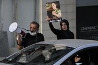 Ibrahim Hoteit, 51, left, and his wife, Hanan, lead a protest for the relatives of victims of the Aug. 4, 2020, Beirut port explosion in Beirut, Lebanon, Saturday, July 10, 2021. Hoteit, whose brother was killed in the blast, has become the face of calls for justice from the families of the victims. (AP Photo/Hassan Ammar)