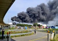 A dark cloud of smoke rises above the chemical park in Leverkusen, Germany, Tuesday, July 27, 2021. Firefighters from the site fire department are on duty. (Mirko Wolf/dpa via AP)
