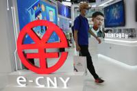 A visitor passes by a logo for the e-CNY, a digital version of the Chinese Yuan, displayed during a trade fair in Beijing, China, Sunday, Sept. 5, 2021. China's central bank on Friday, Sept. 24, 2021 declared all transactions involving Bitcoin and other virtual currencies illegal, stepping up a campaign to block use of unofficial digital money. It is developing an electronic version of the country's yuan for cashless transactions that can be tracked and controlled by Beijing. (AP Photo/Ng Han Guan)