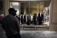 """FILE - In this Nov. 4, 2020, file photo, a man stands in front of a broken display window at a retail store during protests in Portland, Ore. Police in Portland say they believe a new state law prohibits officers from directly intervening when people smash storefronts and cause mayhem. The measure passed this year prohibits the use of crowd control methods like pepper spray and rubber bullets """"unless use of force is otherwise authorized by statute."""" (AP Photo/Marcio Jose Sanchez, File)"""