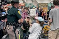 FILE - In this Thursday, Oct. 13, 2021 file photo, New Hampshire State Police remove an audience member, who interrupted proceedings, during a meeting of New Hampshire's Executive Council in Concord, N.H. Republicans in New Hampshire are struggling to contain a wing of their party that is promoting conspiracy views around the Covid-19 vaccine and pushing back, sometimes aggressively, regarding federal mandates to get the shot. (AP Photo/Holly Ramer, File)
