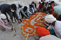 Family members and relatives bow their heads as they pray after burying a person who died of reasons other than COVID-19 in a shallow sand grave on the banks of river Ganges in Prayagraj, India, Sunday, May 16, 2021. Police are reaching out to villagers in northern India to investigate the recovery of bodies buried in shallow sand graves or washing up on the Ganges River banks, prompting speculation on social media that they were the remains of COVID-19 victims. (AP Photo/Rajesh Kumar Singh)