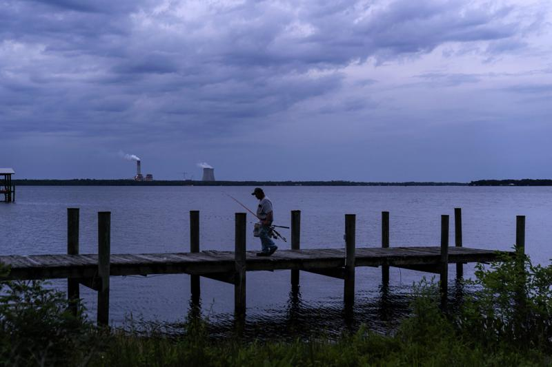 A fisherman walks along a dock on the St. Johns River as a coal-fired power plant stands in the background, in Palatka, Fla., Wednesday, April 14, 2021. After months in a prison cell, Warren Williams longed to fish the St. Johns again. He looked forward to spending days outdoors in his landscaping job, and to writing poems and music in his free time. (AP Photo/David Goldman)