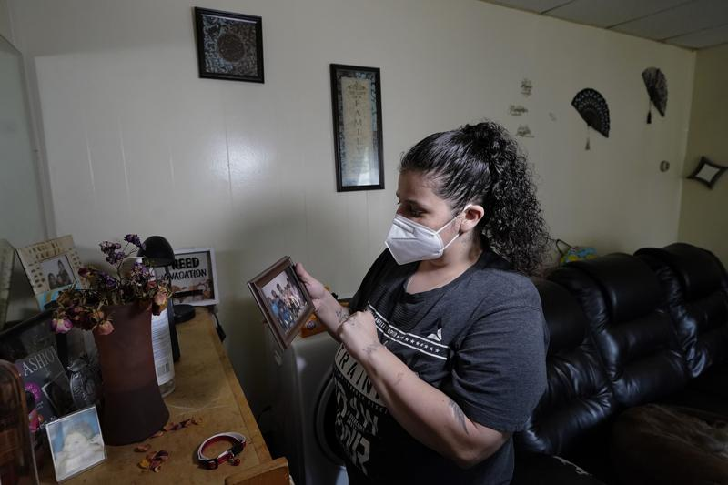 Roxanne Schaefer holds a photograph in the living room of her apartment, in West Warwick, R.I., Tuesday, July 27, 2021. Schaefer, who is months behind on rent, is bracing for the end to a CDC federal moratorium Saturday, July 31, 2021, a move that could result in millions of people being evicted just as the highly contagious delta variant of the coronavirus is rapidly spreading. (AP Photo/Steven Senne)