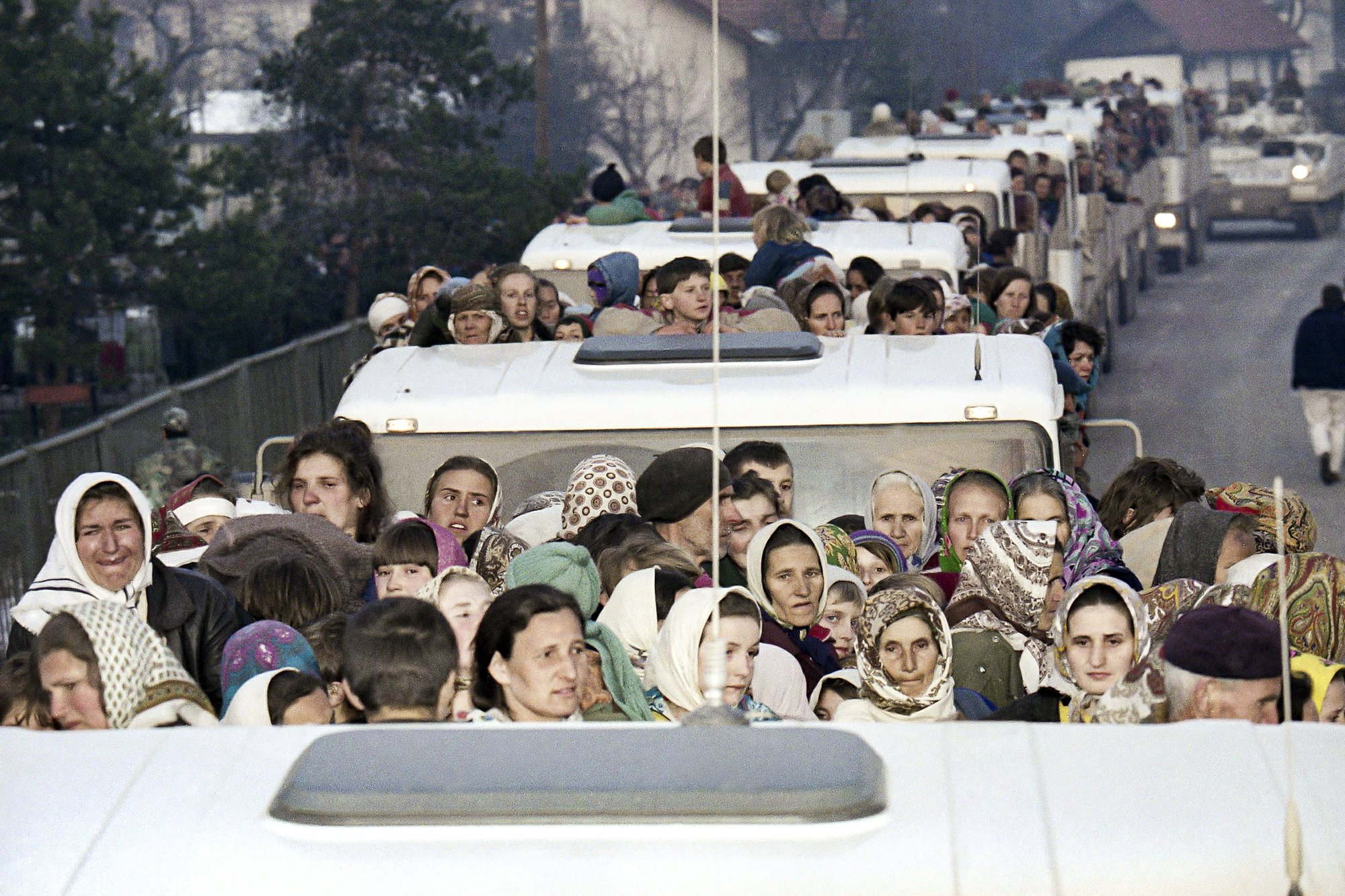 FILE- In this Monday, March 29, 1993 file picture, more than 2,000 refugees from the besieged Muslim enclave of Srebrenica arrive on a United Nations convoy, in Tuzla.  Survivors of the genocide in the eastern Bosnian town of Srebrenica, mainly women, will on Saturday July 11, 2020, commemorate the 25th anniversary of the slaughter of their fathers and brothers, husbands and sons.  At least 8,000 mostly Muslim men and boys were chased through woods in and around Srebrenica by Serb troops in what is considered the worst carnage of civilians in Europe since World War II. The slaughter was also the only atrocity of the brutal war that has been confirmed an act of genocide. (AP Photo/Michel Euler, File)