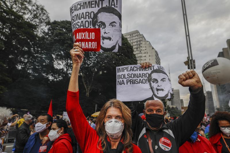 """Demonstranten halten Schilder mit der Aufschrift auf Portugiesisch;  """"Amtsenthebung jetzt! Bolsonaro im Gefängnis"""" während eines Protests gegen den brasilianischen Präsidenten Jair Bolsonaro und seinen Umgang mit der COVID-19-Pandemie auf der Avenida Paulista in Sao Paulo, Brasilien, Samstag, 19. Juni 2021. Die Zahl der COVID-19-Todesopfer in Brasilien wird erwartet in der Nacht zum Samstag den Meilenstein von 500.000 Toten zu übertreffen.  (AP-Foto/Marcelo Chello)"""