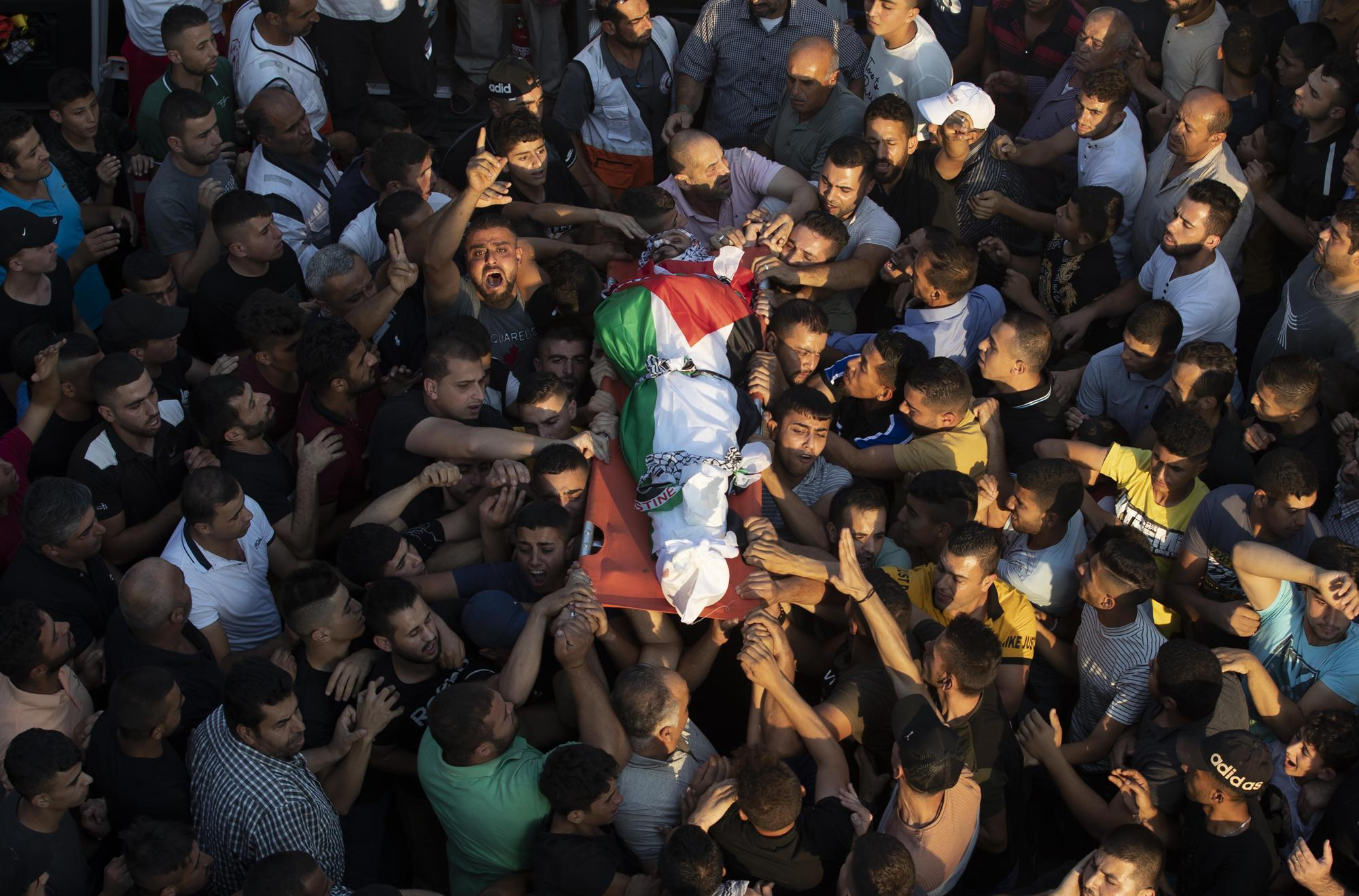 Palestinians carry the body of Imad Dwekat, 37, during his funeral in the village of Beita, south of the West Bank city of Nablus, Friday, Aug. 6, 2021. Dwekat was killed during clashes with Israeli security forces following a protest in the West Bank on Friday. (AP Photo/Majdi Mohammed)
