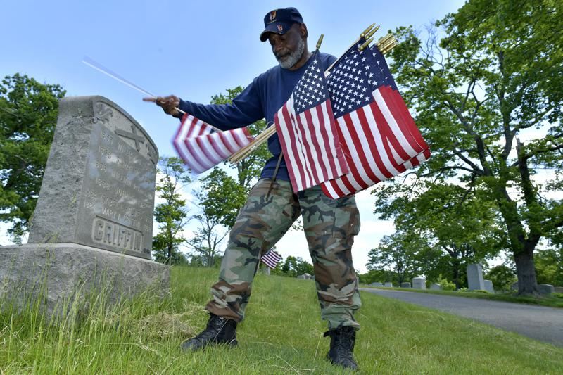 Bob Workman of Boston, a retired Marine Gunnery Sgt., and past commander of the Boston Police VFW, replaces flags at veteran's graves ahead of Memorial Day on Thursday, May 27, 2021, in the Fairview Cemetery in Boston. After more than a year of isolation, American veterans are embracing plans for a more traditional Memorial Day. After more than a year of isolation, military veterans say wreath-laying ceremonies, barbecues at local vets halls and other familiar traditions are a welcome chance for them to reconnect with fellow service members and renew solemn traditions honoring the nation's war dead. (AP Photo/Josh Reynolds)