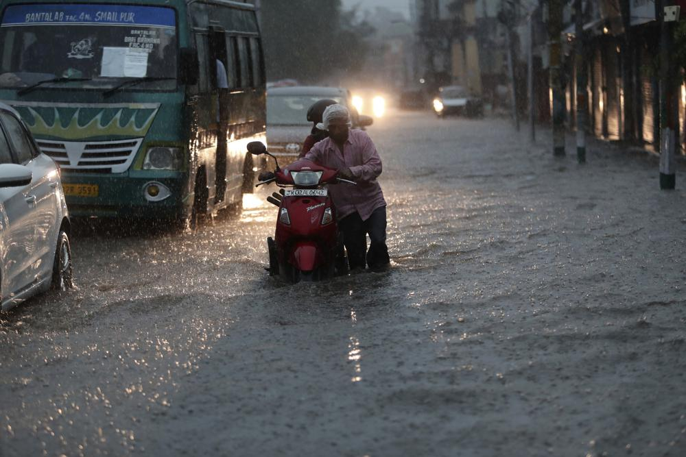 A man pushes a two wheeler through a flooded street during monsoon rains Jammu, India, Monday, July 12, 2021. India's monsoon season runs from June to September.