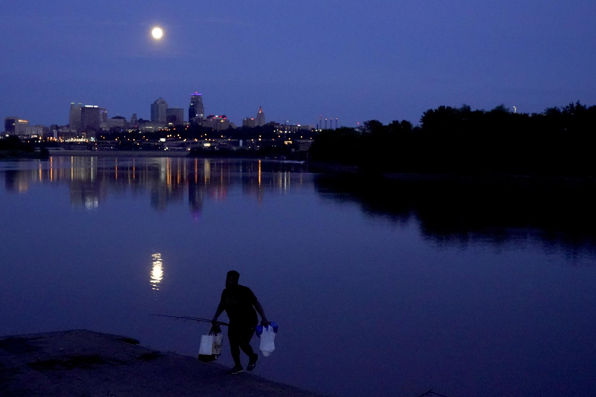 A man leaves after fishing in the Missouri River as the nearly full moon rises beyond the downtown skyline, late Tuesday, May 25, 2021, in Kansas City, Mo. (AP Photo/Charlie Riedel)