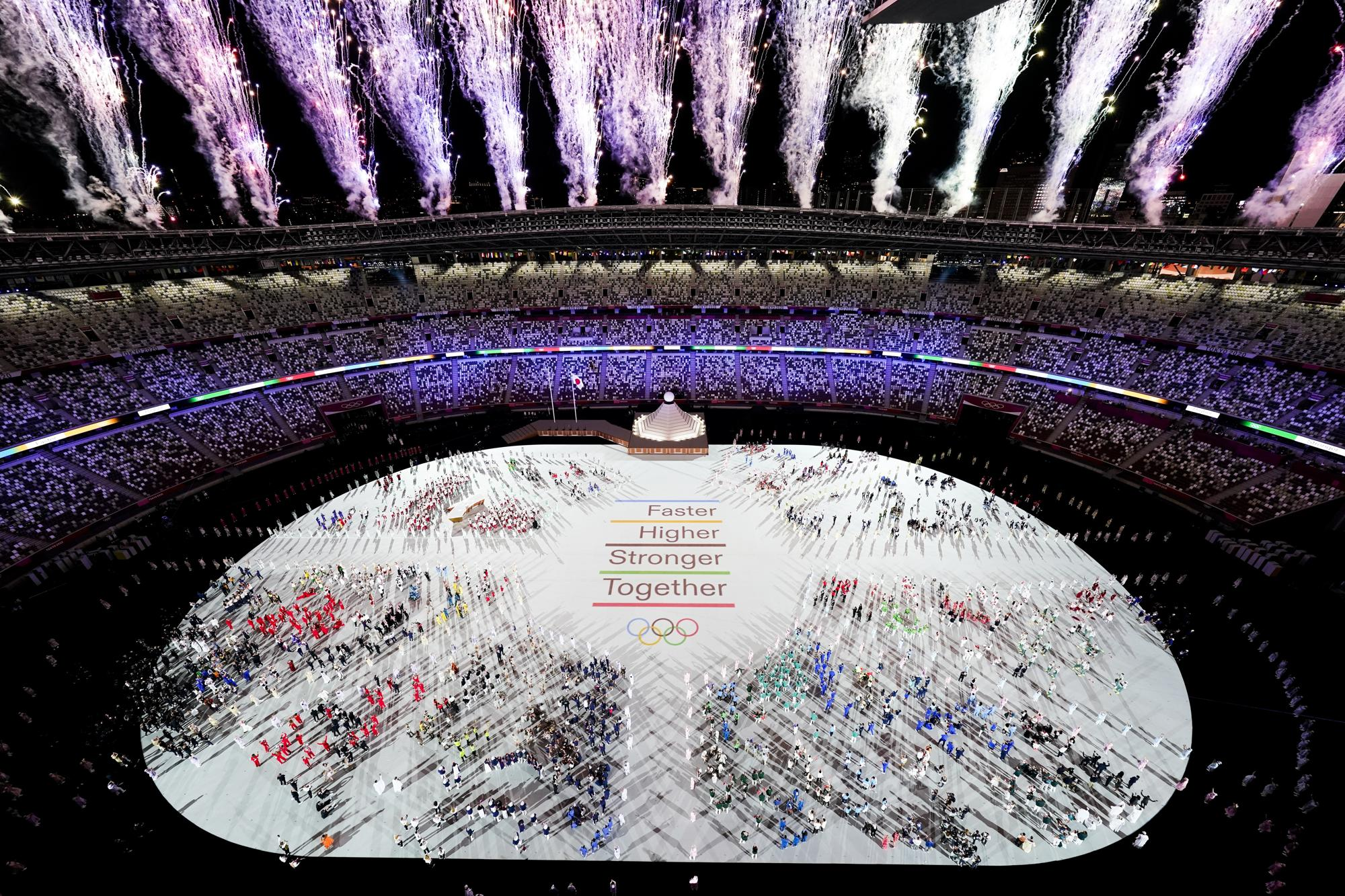 Athletes are seen with fireworks during the opening ceremony at the Olympic Stadium at the 2020 Summer Olympics, Friday, July 23, 2021, in Tokyo. (AP Photo/Morry Gash)