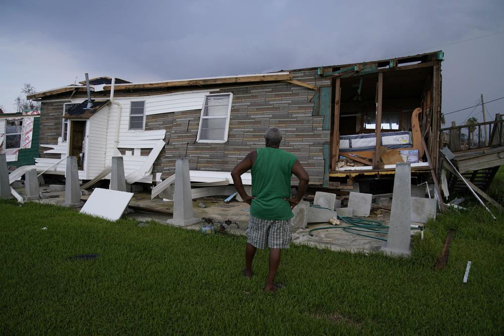 Randy Manuel surveys his and his mother's hurricane destroyed home in the aftermath of Hurricane Ida, Saturday, Sept. 4, 2021, in Dulac, La. (AP Photo/John Locher)