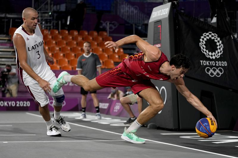 Belgium's Rafael Bogaerts, right, chases a loose ball as Latvia's Edgars Krumins (3) watches during a men's 3-on-3 basketball game at the 2020 Summer Olympics, Saturday, July 24, 2021, in Tokyo, Japan. (AP Photo/Jeff Roberson)