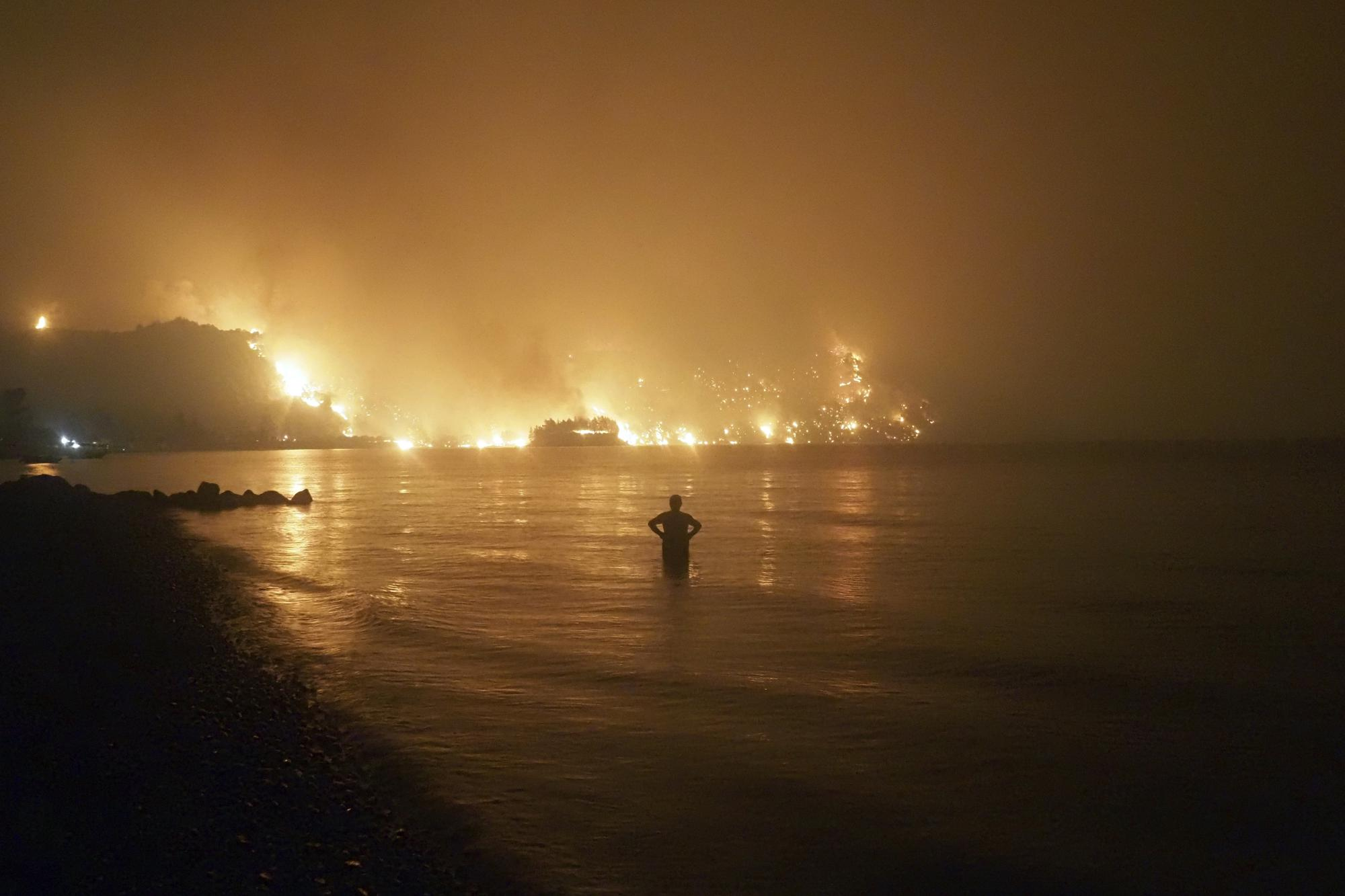 A man watches the flames as wildfire approaches Kochyli beach near the village of Limni, Greece, on the island of Evia, about 160 kilometers (100 miles) north of Athens, late Friday, Aug. 6, 2021, as wildfires raged uncontrolled through Greece and Turkey. (AP Photo/Thodoris Nikolaou)