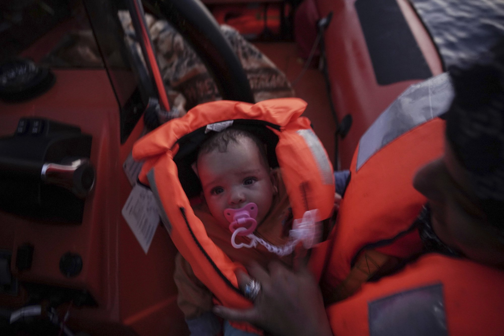 In this Sept. 19, 2019 photo, 4-month-old Mira is held by her mother during a rescue by the Ocean Viking humanitarian ship in the Mediterranean Sea. Her mother says their family escaped Libya after their home was destroyed in the war. (AP Photo/Renata Brito)
