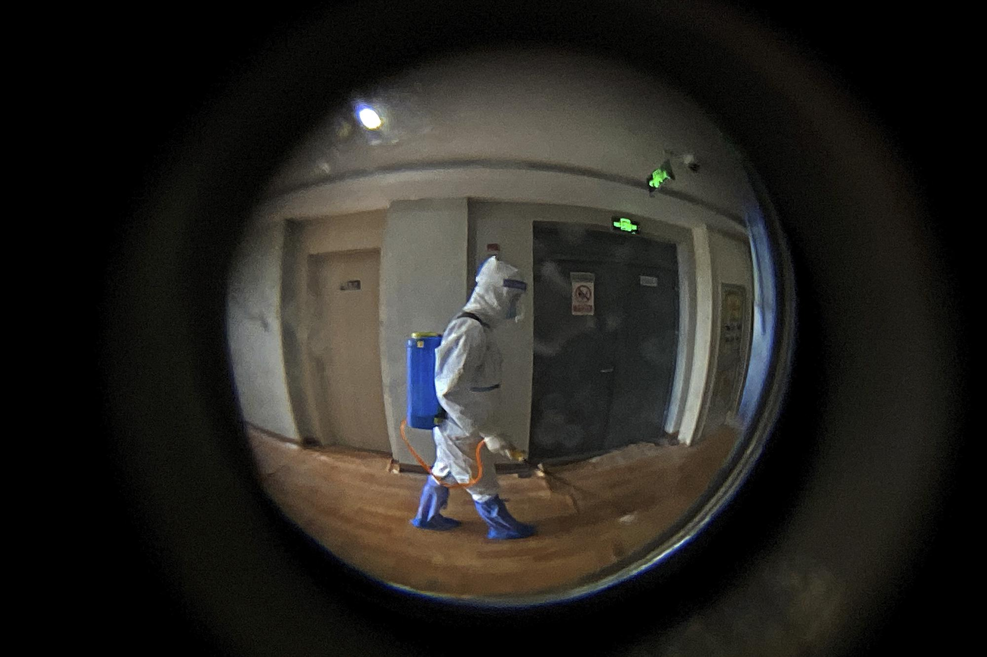 Seen through a door peephole, a medical worker wearing a protective clothing disinfects the corridor of a hotel used for foreigners to stay during a period of health quarantine in Shanghai, China, Thursday, Aug. 12, 2021. More than 30 Chinese officials have been fired or received other punishments over accusations they failed to respond properly to the latest surge of the coronavirus in the country. (AP Photo/Andy Wong)