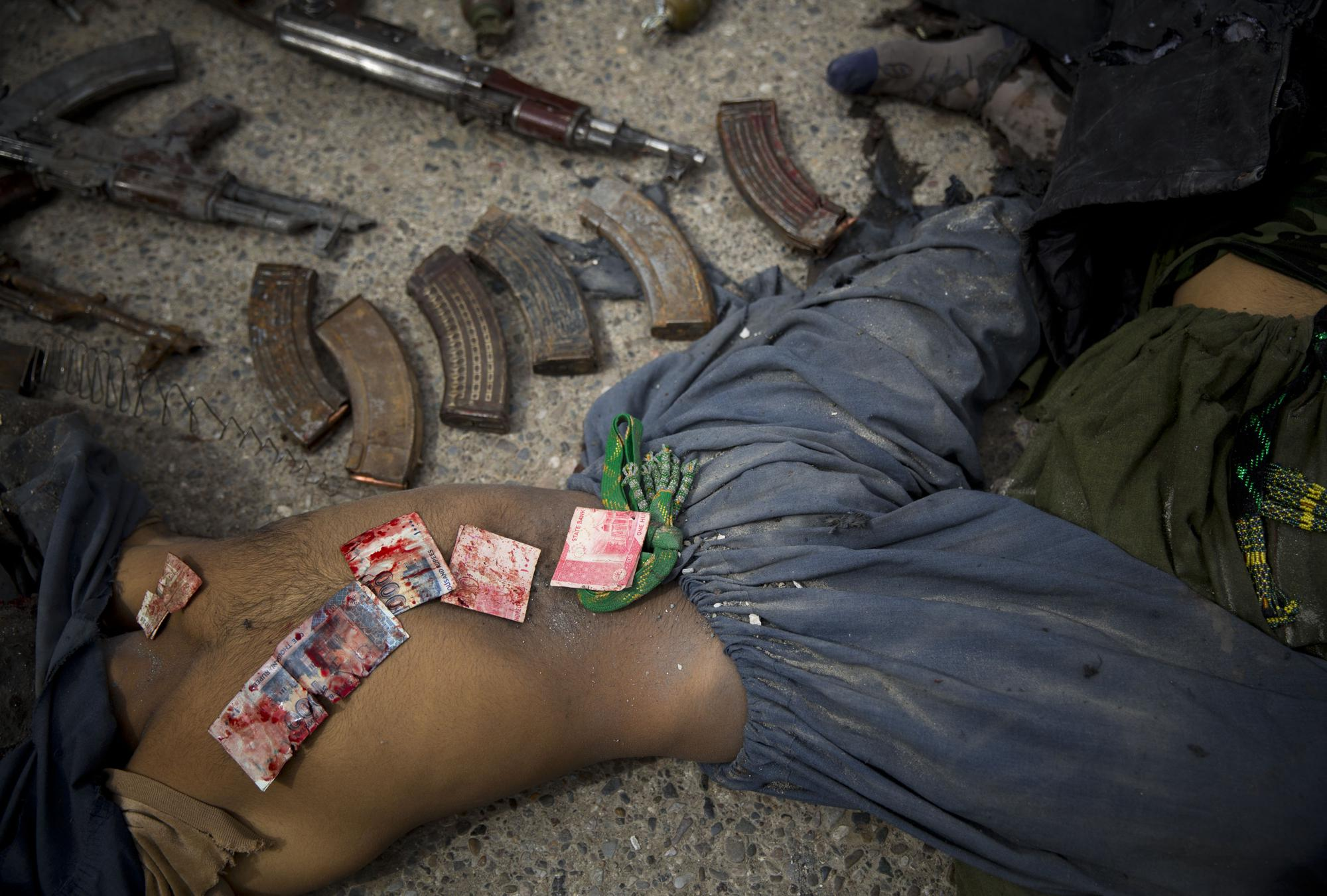 Pakistani bank notes covered in blood are displayed on the body of a dead suicide bomber after police found them in his pocket in the center of Kandahar, Afghanistan, Wednesday, March 12, 2014, after an attack on the former Afghan intelligence headquarters. Police officials said three insurgents who tried to storm the former headquarters of Afghanistan's intelligence service in southern Kandahar died in a gunbattle with security forces. (AP Photo/Anja Niedringhaus)